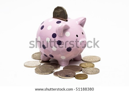 piggybank with coin in it and spread around it - stock photo