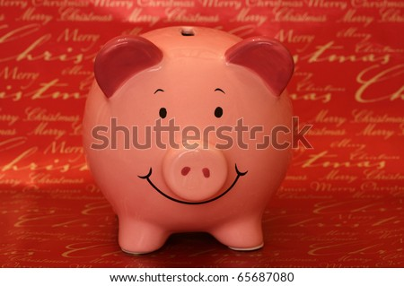 Piggybank with Merry Christmas background in studio - stock photo