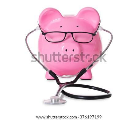 Piggybank with stethoscope and eyeglasses isolated over white background - stock photo