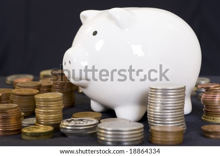 Piggybank with various international currencies on a black background. - stock photo