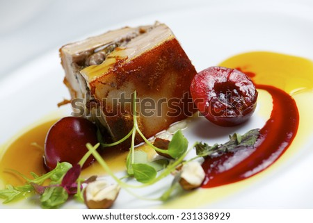 Piglet with cherries in a white plate. - stock photo