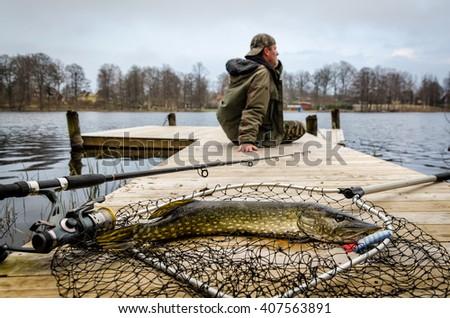 Pike fishing in spring scenery - stock photo