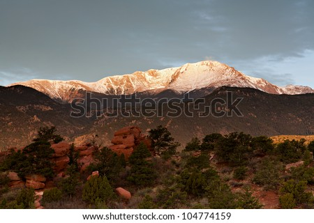 Pike's Peak is illuminated by the morning sun while gray clouds cover the sky above the mountain.