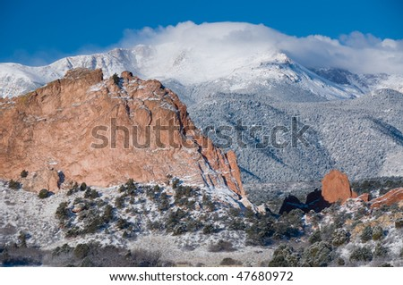 Pikes Peak covered by a white fluffy cloud in February as seen from the Garden of the Gods Park near Colorado Springs, Colorado. - stock photo
