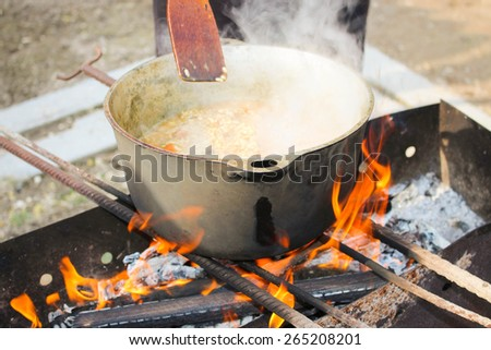 Pilaf cooking on a fire.  - stock photo