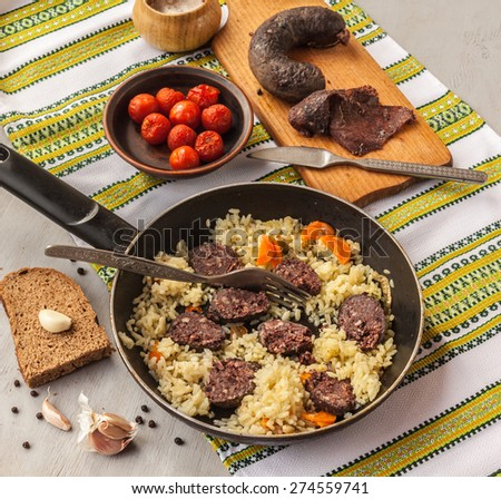 Pilaf in a pan and black pudding and pickled tomatoes on the embroidered towel - stock photo