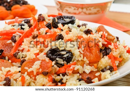 Pilaf made of rice, fresh carrots and dried plums, grapes, apricots. - stock photo