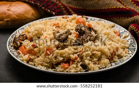 Pilaf on plate with oriental ornament and Traditional Asian breads - churek. Plov.