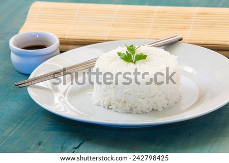 pilaf rice on white plate with two chopstick and soya sauce - stock photo