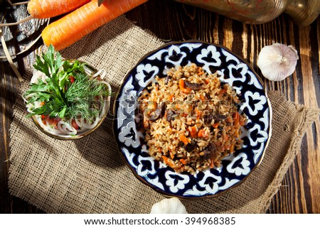 Pilaf - Rice with Meat and Vegetables. Garnished with Onions and Tomatoes Salad - stock photo