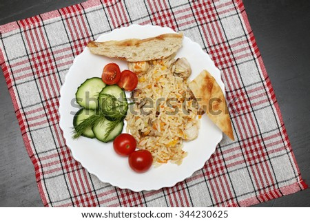 pilaf with chicken pita bread and vegetables on the plate - stock photo