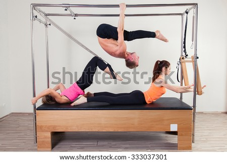 Pilates aerobic instructor a group of three people in cadillac fitness exercise. - stock photo
