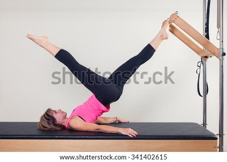 Pilates aerobic instructor woman in cadillac fitness exercise. - stock photo