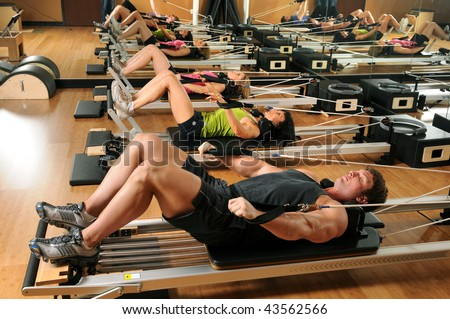 Pilates class with men and women at a gym - stock photo