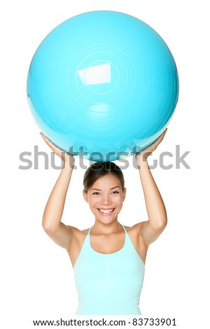 Pilates fitness woman isolated exercising with exercise ball during workout. Beautiful smiling happy mixed race Chinese Asian / Caucasian fit female fitness woman isolated on white background. - stock photo
