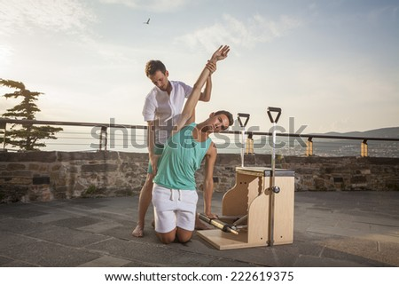 Pilates personal trainer doing class on a machine  outdoors - stock photo