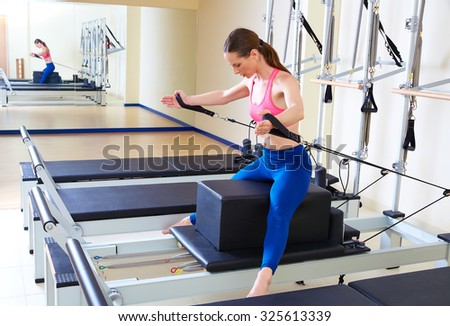 Pilates reformer woman short box horse back exercise workout at gym - stock photo
