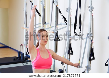 Pilates reformer woman side push through exercise workout at gym indoor - stock photo