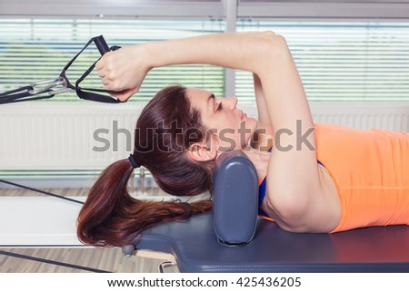 Pilates reformer workout exercises woman at gym indoor - stock photo