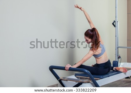 Pilates reformer workout exercises woman brunette at gym indoor. - stock photo