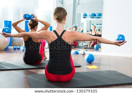 Pilates toning ball in women fitness class rear mirror view