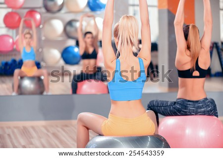 Pilates training. Rear view of two beautiful young women in sports clothing exercising together on fit balls at the gym in front of mirror - stock photo