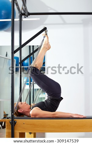 Pilates woman in reformer tower exercise at gym indoor - stock photo