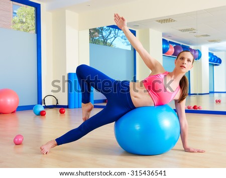 Pilates woman passes fitball exercise workout at gym indoor swiss ball