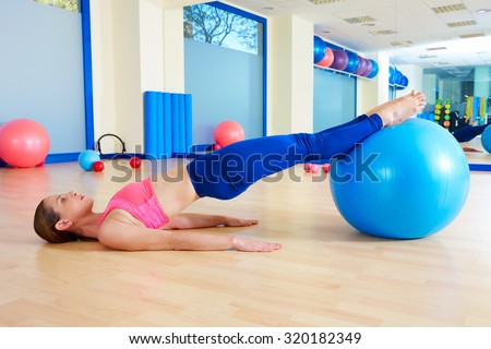 Pilates woman pelvic lift fitball exercise workout at gym indoor swiss ball - stock photo