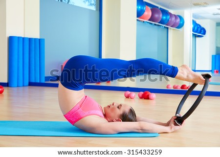 Pilates woman roll over magic ring exercise workout at gym indoor