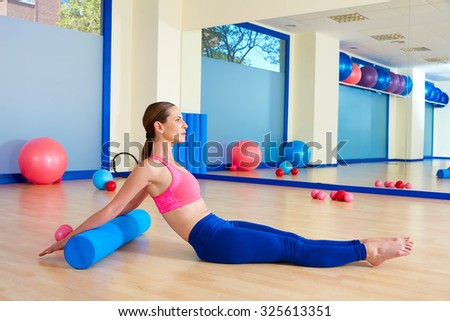 Pilates woman roller roll back exercise workout at gym indoor