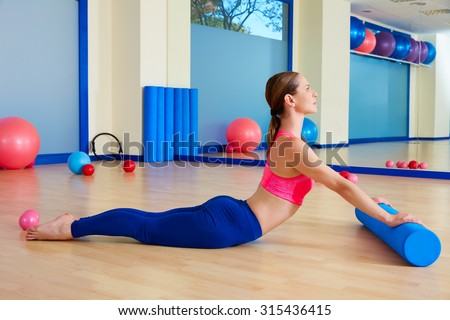 Pilates woman roller swan roll exercise workout at gym indoor - stock photo