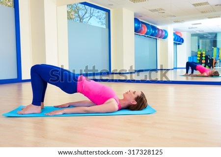 Pilates woman shoulder bridge exercise workout at gym indoor