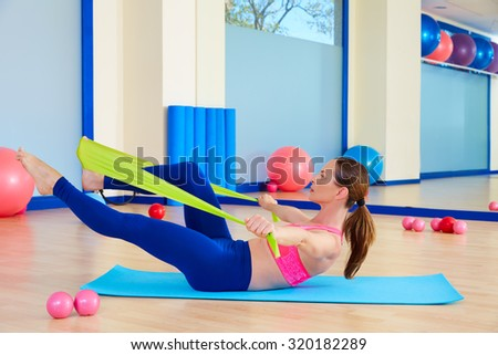 Pilates woman single leg stretch rubber band exercise workout at gym indoor