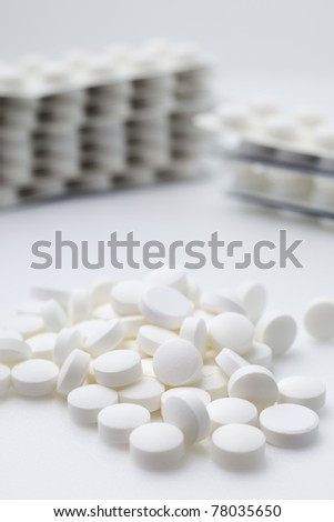 Pile and stacks of white tablets on white background.