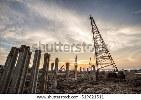 pile crane in construction site at sunset
