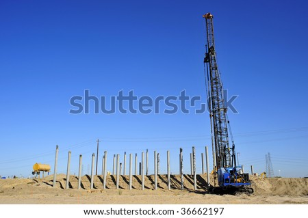 Pile driver works to set precast concrete piles for new bridge - stock photo