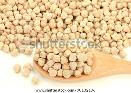 Pile Dry Raw Chick Peas Seeds (very rich of proteins) and in wooden cooking spoon over white background. - stock photo