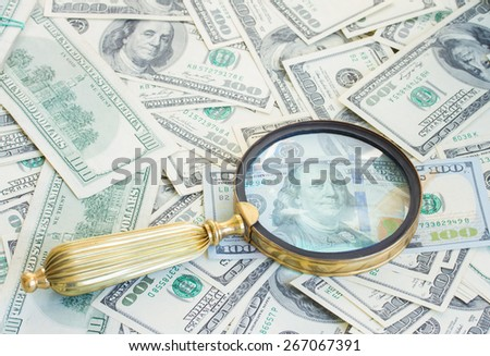 pile of american 100 bill dollars money under manifying glass - stock photo