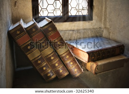Pile of ancient books in front of window