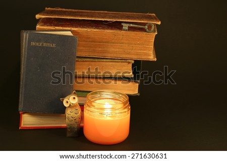 Pile of antique books with King James Bible and candle and owl to show one gains wisdom by reading, especially the Bible. Black background - stock photo