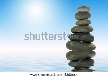 Pile of Balanced Stones in Zen-like Setting with Reflection Representing Meditation. - stock photo