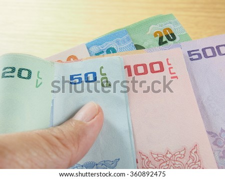 Pile of banknotes in hand, Thai baht money, earn and save money
