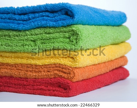 Pile of beautiful fluffy terry towels on a grey background