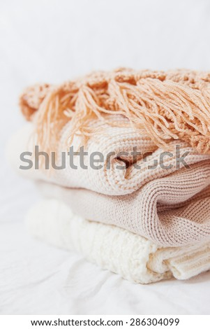 Pile of beige woolen clothes on a white background. Warm knitted sweaters and scarfs are folded in one heap.  - stock photo
