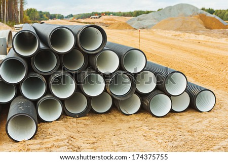 pile of big pipes on construction site - stock photo