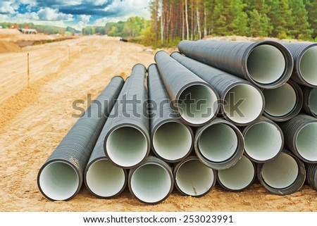 pile of big water pipes on construction site  - stock photo