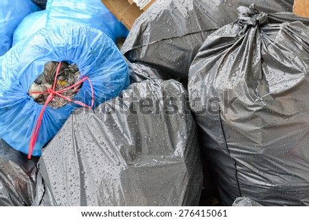Pile of black and blue plastic trash bags full of garbage - stock photo