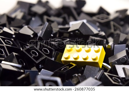Pile of black color building blocks with selective focus and highlight on one particular yellow block using available light - stock photo