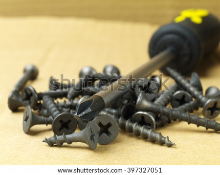 pile of black drywall screws and Phillips screwdriver, macro, shallow depth of field